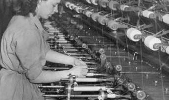 weaver controlling a mechanized loom